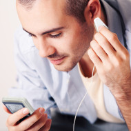 Portrait of a relaxed young guy sitting on bed and listening to music on headphone